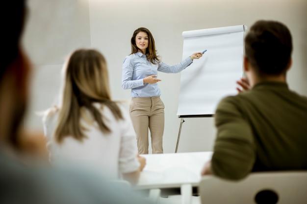Kreativer positiver weiblicher führer, der über unternehmensplan mit studenten während der werkstatt spricht Premium Fotos
