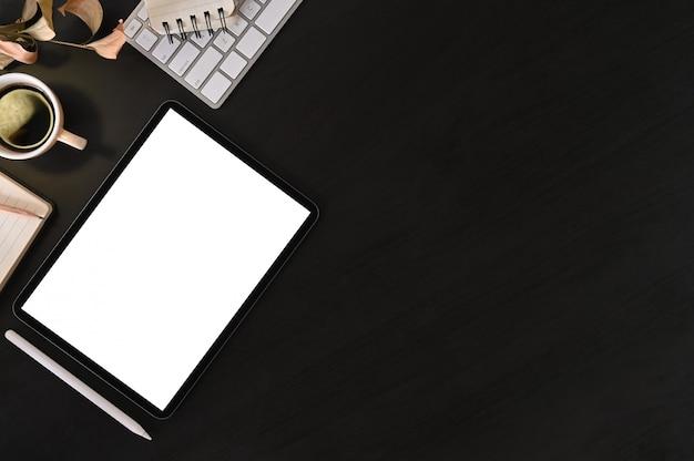 Kreativer schreibtischarbeitsplatz mit modelltablet-computer und büroausstattung auf schwarzer tabelle, draufsicht. Premium Fotos
