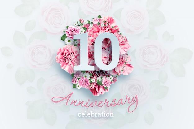 Kreatives beschriften von 10 zahlen und von jahrestagsfeiertext auf rosa blumen, feierereignis, schablone, flieger Premium Fotos