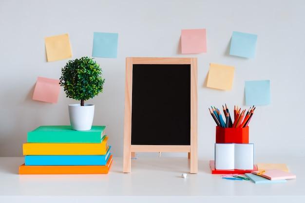 Kreatives desktop-layout des schülers mit buntem briefpapier, buntstiften und hellen büchern auf einem weißen wandhintergrund. Premium Fotos