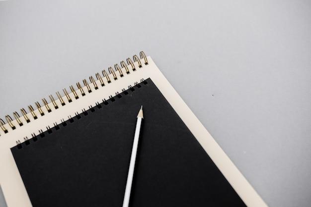 Kreatives flachlagefoto des arbeitsplatzschreibtischs mit den weißen und schwarzen notizbüchern Premium Fotos