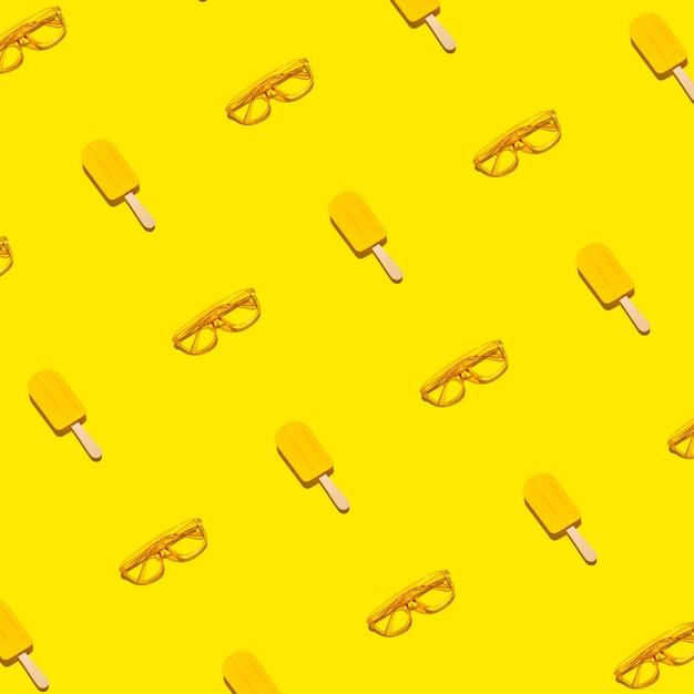 Kreatives gelbes sommermuster von eis am stiel und sonnenbrille auf hellem abstraktem gelbem hintergrund Premium Fotos