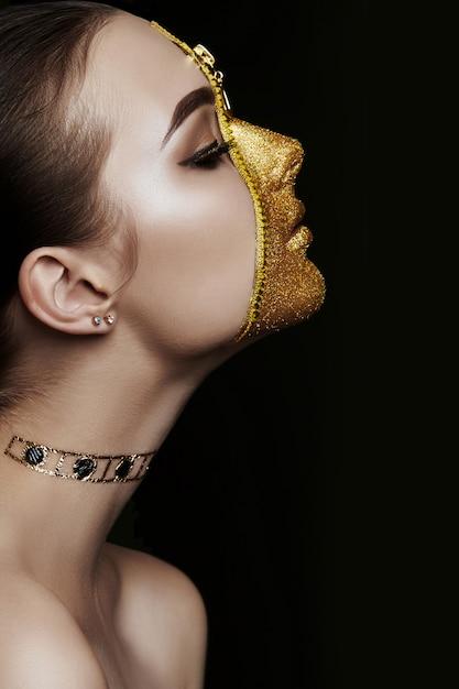 Kreatives grimmiges make-upgesicht der goldenen farbreißverschlusskleidung des mädchens auf haut. mode schönheit Premium Fotos