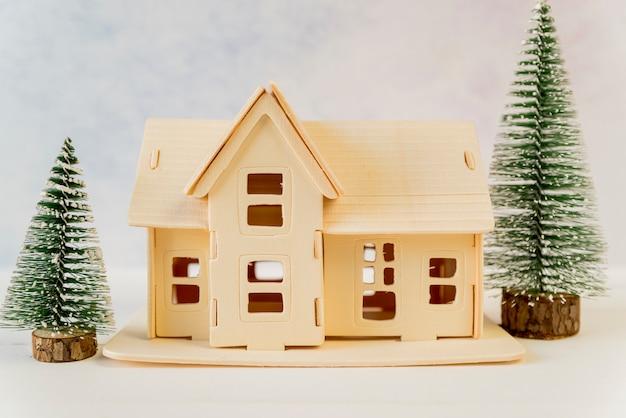 Kreatives haus mit grünen weihnachtsbäumen auf strukturiertem hintergrund Kostenlose Fotos