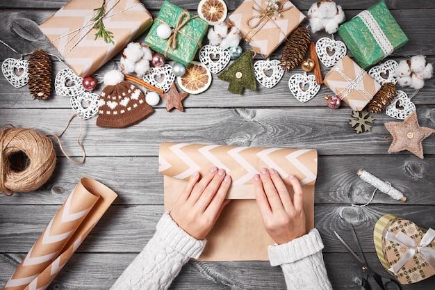Kreatives hobby. weihnachtsgeschenke mit werkzeugen und dekorationen. verpackungsgeschenke auf holztisch, draufsicht. Premium Fotos