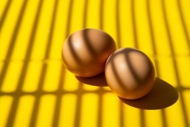 Kreatives lebensmittelfoto, abstrakter gelber hintergrund mit zwei rohen eiern. Premium Fotos