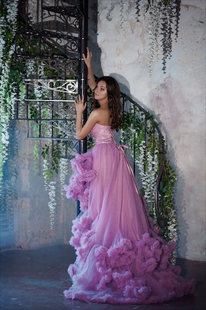 Kreatives porträt einer modefrau im herrlichen langen rosa romantischen kleid Premium Fotos