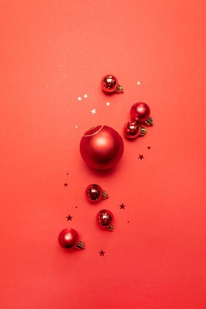 Kreatives weihnachtsplakat der roten kugeln und der roten sterne des funkelns auf rot. flache lage, draufsicht, copyspace Premium Fotos