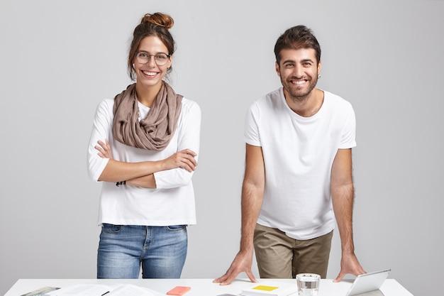Kreativteam von zwei glücklichen männlichen und weiblichen kollegen in freizeitkleidung, die am schreibtisch stehen, Kostenlose Fotos