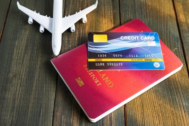 Kreditkarte auf pass und flugzeugmodell auf holztisch gesetzt, vorbereitung für das reisekonzept Premium Fotos