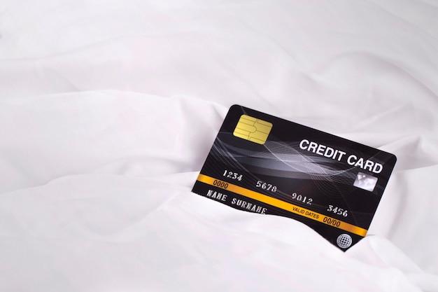 Kreditkarte auf weißem stoffgewebebeschaffenheitshintergrund Premium Fotos