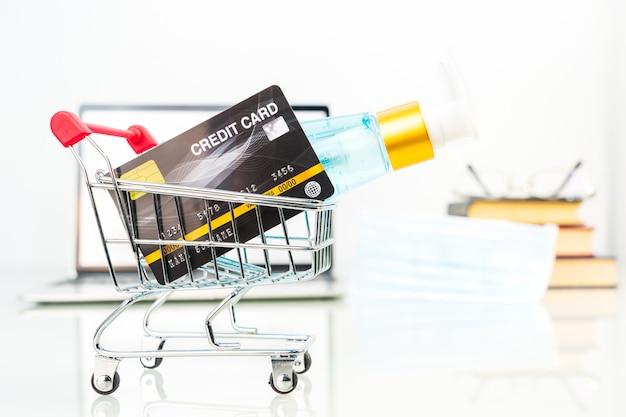 Kreditkarte im einkaufswagen vor laptop-bildschirm mit alkohol-gel-flasche Premium Fotos
