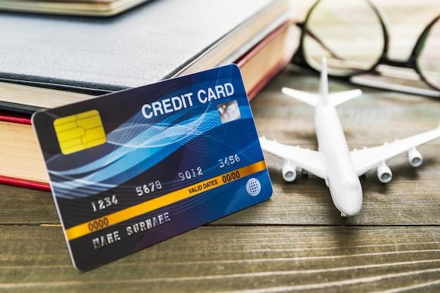 Kreditkarten- und flugzeugmodell auf holztisch Premium Fotos