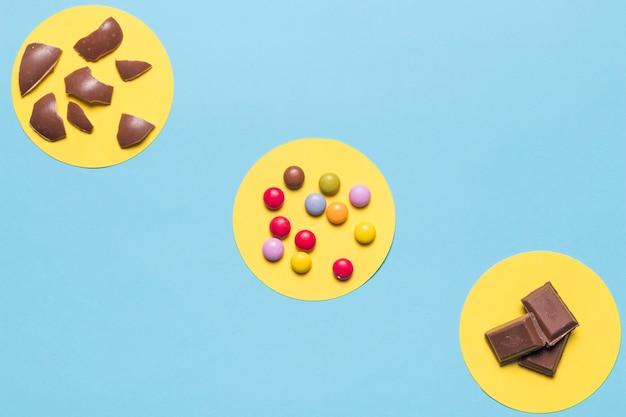 Kreisförmiger gelber rahmen über den bunten edelsteinsüßigkeiten; ostereierschalen und schokoladenstücke auf blauem hintergrund Kostenlose Fotos