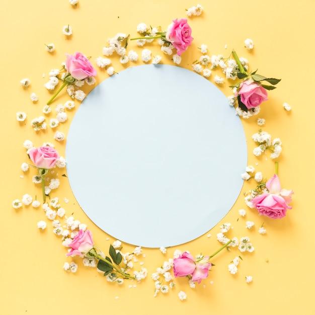 Kreisförmiger leerer rahmen umgeben mit blumen auf gelber oberfläche Kostenlose Fotos