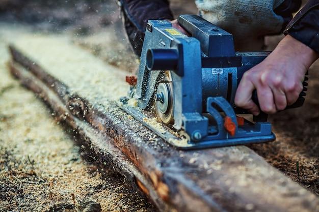Kreissäge zum schneiden von brettern in die hände des bauherrn, der mann sägte stangen, bau- und renovierungs-, reparatur- und bauwerkzeuge Premium Fotos