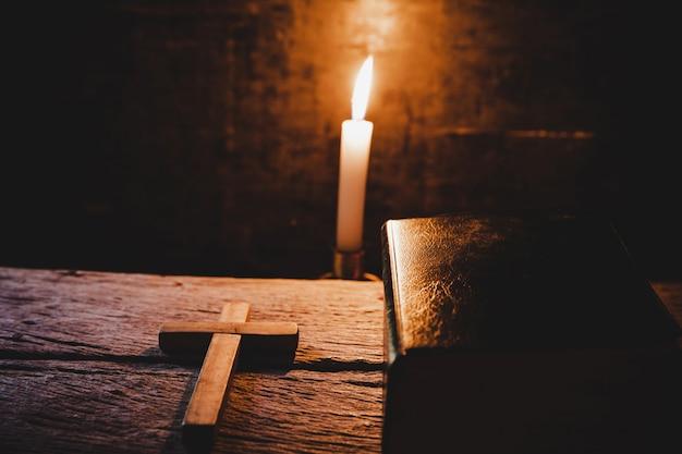Kreuzen sie mit bibel und kerze auf einem alten eichenholztisch. Kostenlose Fotos