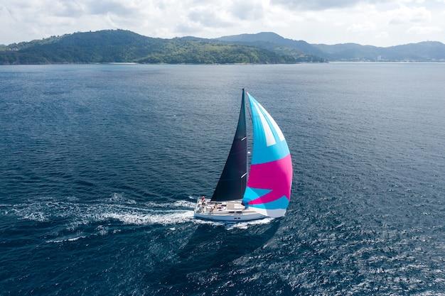 Kreuzfahrturlaub. luftaufnahme der yacht mit rosa segel auf meerwasser Premium Fotos