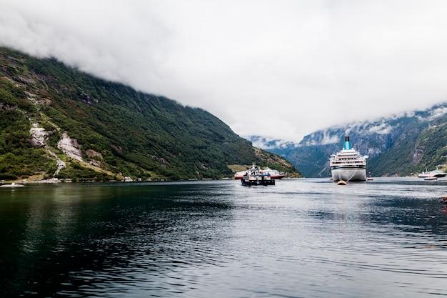 Kreuzschiff am meer mit bergen Kostenlose Fotos