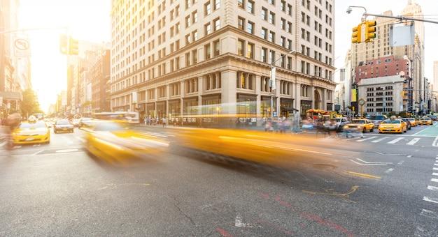 Kreuzung der verkehrsreichen straße in manhattan, new york, bei sonnenuntergang Premium Fotos