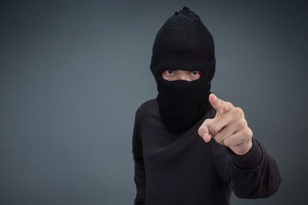 Kriminelle tragen eine maske in schwarz auf grau Kostenlose Fotos