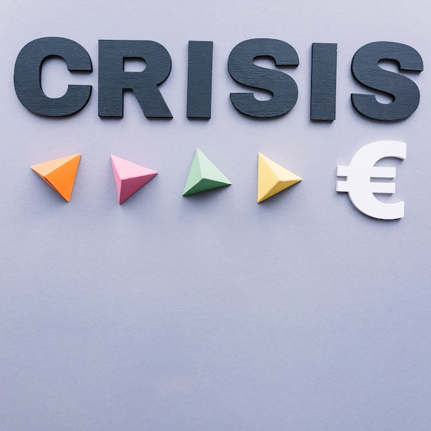 Krisenwort mit bunten dreieckigen pyramiden und eurozeichen auf grauem hintergrund Kostenlose Fotos