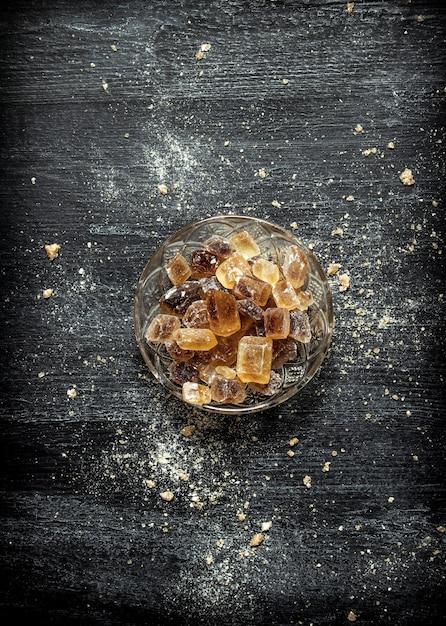 Kristalliner rohrzucker in einer untertasse auf schwarzem rustikalem tisch. Premium Fotos