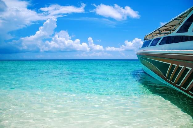 Kristallklares wasser und schnellboot des schönen landschaftsmeerblick-strandes Premium Fotos