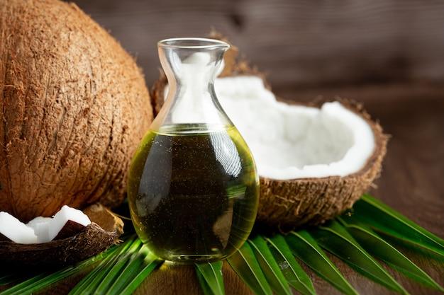 Krug kokosöl mit kokosnuss auf dunklem hintergrund Kostenlose Fotos