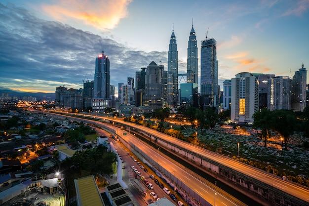 Kuala lumpur-skyline und -wolkenkratzer mit landstraßenstraße nachts in kuala lumpur, malaysia. asien. Premium Fotos