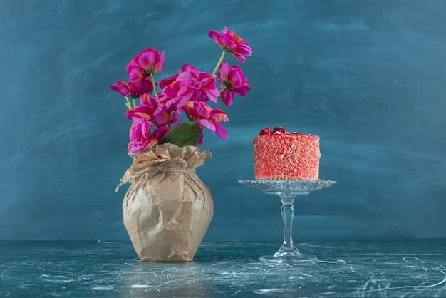 Kuchen auf einem sockel neben einer blumenvase auf blau. Kostenlose Fotos