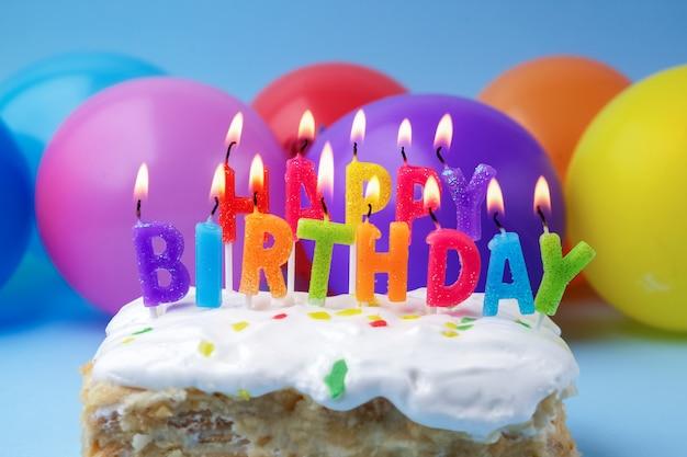 Kuchen mit geburtstagsgrüßen von brennenden kerzen auf einem farbigen hintergrund Premium Fotos