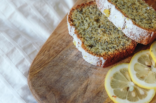 Kuchen mit mohn und zitronenschale, bestreut mit puderzucker. cupcake mit zitrone auf einem holzbrett. Premium Fotos