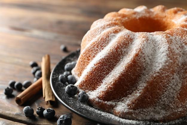 Kuchen mit puderzucker und blaubeere auf hölzernem hintergrund, raum für text Premium Fotos