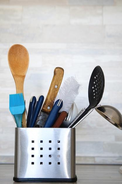 Küchen-tischbesteck im metallstand mit sauberen geräten auf grau Premium Fotos