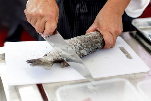 Küchenchef bei der arbeit, küchenchef beim filetieren von fischen in der küche, küchenchef beim filetieren von fischen in der restaurantküche Premium Fotos