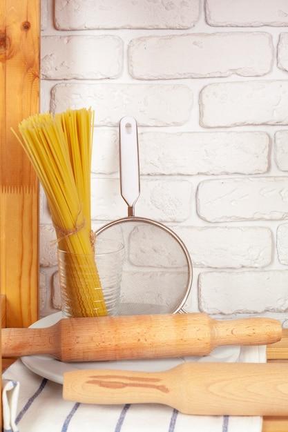 Küchengeräte und dishware auf hölzernem regal Premium Fotos