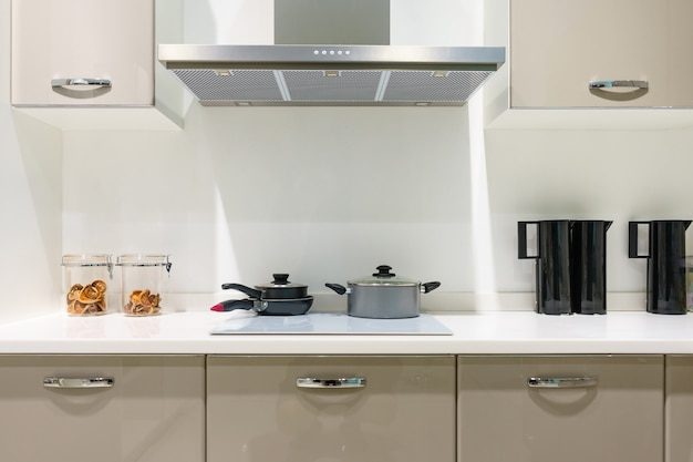Küchenmöbel mit modernen küchengeräten wie dunstabzugshaube, schwarzem induktionsherd und backofen Premium Fotos