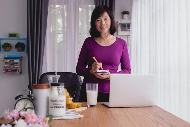 Küchentisch mit asiatischem älterem schreiben auf briefpapier für die zubereitung des lebensmittels. Premium Fotos