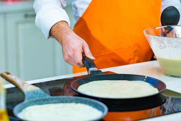 Küchenvorbereitung: der küchenchef brät frische pfannkuchen in zwei pfannen Premium Fotos
