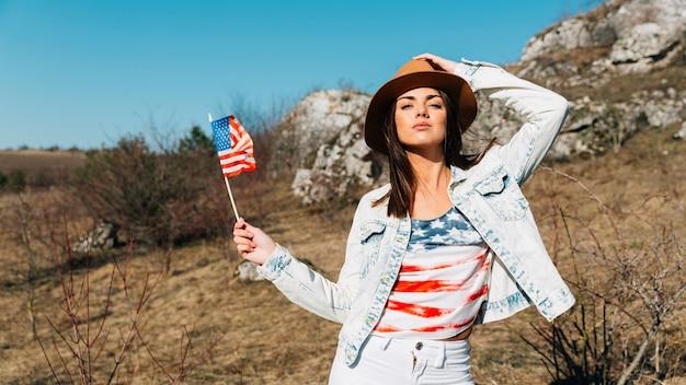 Kühle junge frau mit usa-flagge, die in der natur aufwirft Kostenlose Fotos