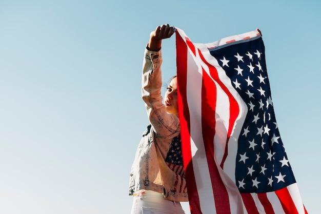 Kühlen sie die junge frau ab, die die amerikanische flagge hält, die über schulter schaut Kostenlose Fotos