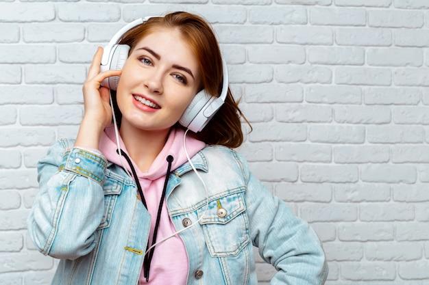 Kühles mädchen der hübschen mode, das musik in den kopfhörern hört Premium Fotos