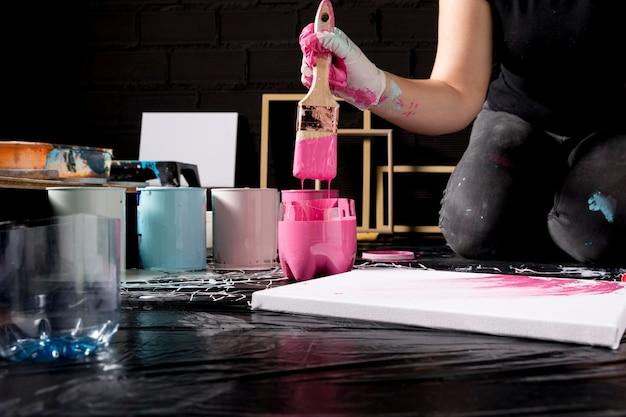 Künstler, der pinsel verwendet, um leinwand zu malen Kostenlose Fotos