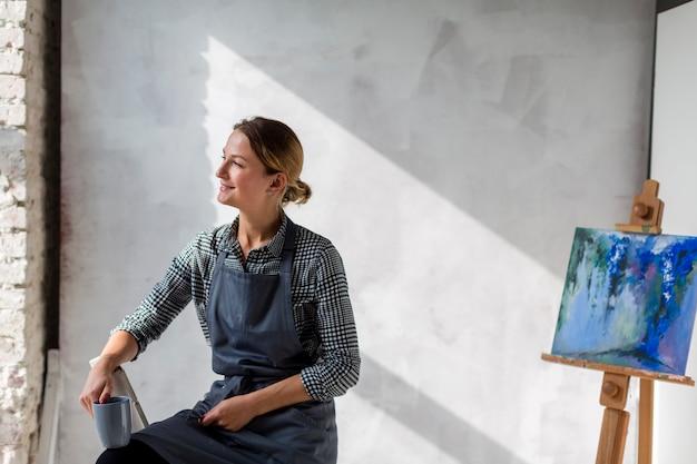 Künstlerfrau, die auf stuhl mit gestell und malerei aufwirft Kostenlose Fotos