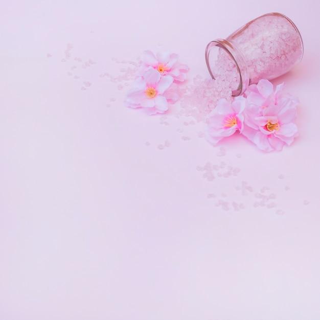 Künstliche blumen und verschüttetes salz vom glas auf rosa hintergrund Kostenlose Fotos