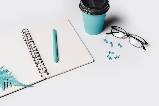 Künstliche farnblätter und -stift auf weißem leerem gewundenem notizbuch mit kaffeetasse; brille und push-pin Kostenlose Fotos