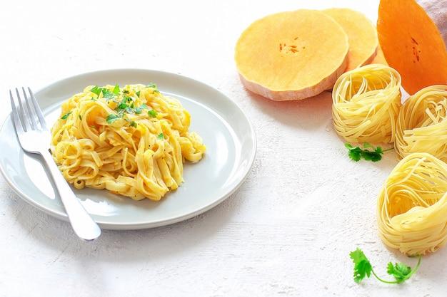 Kürbis alfredo fettucine pasta in einer keramikplatte mit frischen rohen butternut-kürbis-scheiben. herbstessen zum mittagessen. butternut-kürbis-rezept. Kostenlose Fotos