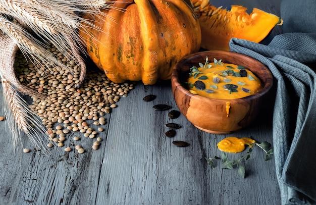 Kürbis-linsen-cremesuppe in olivenholzschale mit thymian Premium Fotos
