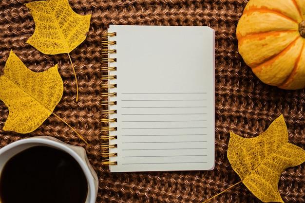 Kürbis, notizbuch, tasse kaffee und blätter auf braun Premium Fotos
